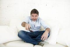 Hombre feliz joven que ve la TV el sentar en casa del sofá de la sala de estar que parece relajado gozando de la televisión Imagen de archivo libre de regalías