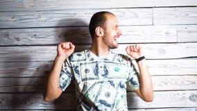 Hombre feliz loco en rejoi de la camiseta del dólar en las sonrisas y los saltos del éxito para la alegría Concepto a propósito d almacen de video