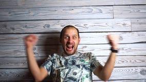 Hombre feliz loco en rejoi de la camiseta del dólar en las sonrisas y los saltos del éxito para la alegría Concepto a propósito d almacen de metraje de vídeo