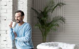 Hombre feliz positivo que se inclina contra la pared Foto de archivo libre de regalías