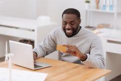 Hombre feliz positivo que sostiene una tarjeta de crédito Imagenes de archivo
