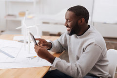 Hombre feliz positivo que usa una tableta Imágenes de archivo libres de regalías