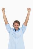 Hombre feliz que celebra éxito con los brazos para arriba Fotografía de archivo