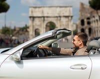 Hombre feliz que conduce el coche del cabriolé sobre la ciudad de Roma Imagen de archivo libre de regalías