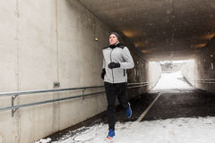 Hombre feliz que corre a lo largo del túnel del subterráneo en invierno Foto de archivo libre de regalías