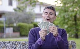 Hombre feliz que cuenta su dinero Fotografía de archivo