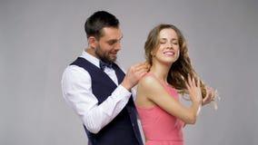 Hombre feliz que da el collar de diamantes a la mujer metrajes