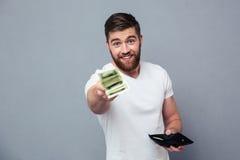 Hombre feliz que da el dinero en la cámara Foto de archivo libre de regalías