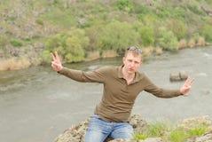 Hombre feliz que da una V-muestra doble en un top de la colina Imagenes de archivo