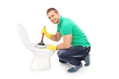Hombre feliz que desatasca un retrete con el émbolo Imagen de archivo libre de regalías