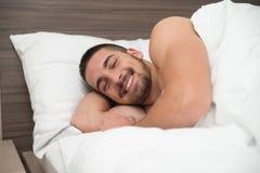 Hombre feliz que despierta en su dormitorio Foto de archivo
