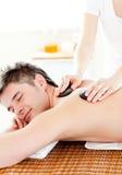 Hombre feliz que disfruta de un masaje posterior con las piedras calientes Imagen de archivo libre de regalías