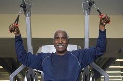 Hombre feliz que ejercita en gimnasio Fotos de archivo libres de regalías