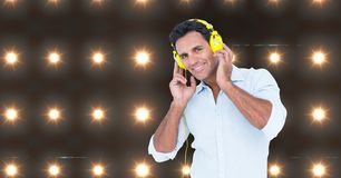 Hombre feliz que escucha la música con las luces en fondo fotos de archivo libres de regalías