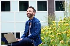 Hombre feliz que escucha la música del ordenador portátil Foto de archivo libre de regalías