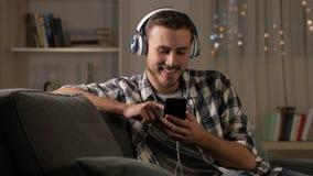 Hombre feliz que escucha la música en el teléfono en la noche