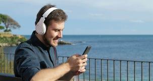 Hombre feliz que escucha la música que se sienta en un banco metrajes