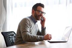 Hombre feliz que habla en el teléfono móvil delante del ordenador portátil imagenes de archivo