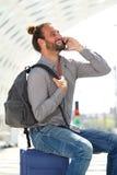 Hombre feliz que habla en el teléfono móvil que se sienta en la maleta Imagen de archivo