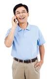 Hombre feliz que habla en el teléfono móvil mientras que se coloca Imágenes de archivo libres de regalías