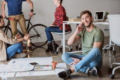 Hombre feliz que habla en smartphone en oficina Imagen de archivo libre de regalías