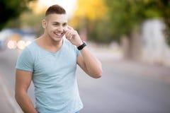 Hombre feliz que hace llamada en la calle de la ciudad Imagenes de archivo