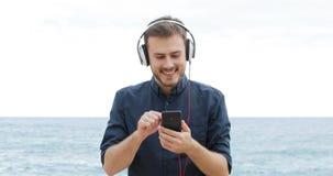 Hombre feliz que hojea y que escucha la música metrajes