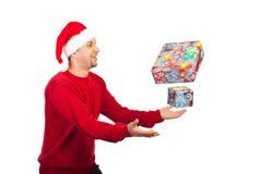 Hombre feliz que intenta coger los regalos de la Navidad Foto de archivo