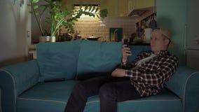 Hombre feliz que juega al juego en su móvil mientras que miente en el sofá 4K almacen de metraje de vídeo