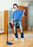 Hombre feliz que juega y que baila con la escoba en casa Imagenes de archivo
