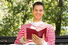 Hombre feliz que lee un libro Fotografía de archivo