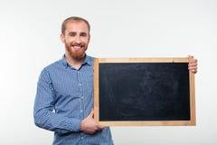 Hombre feliz que lleva a cabo al tablero en blanco Foto de archivo libre de regalías