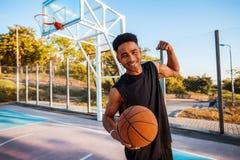 Hombre feliz que lleva a cabo el baloncesto, bola de la calle, hombre que juega, competencias de deporte, retrato al aire libre,  Imagenes de archivo