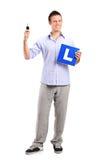 Hombre feliz que lleva a cabo un clave y un L placa del coche Foto de archivo libre de regalías