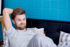 Hombre feliz que mira el medios contenido en un teléfono elegante Foto de archivo libre de regalías