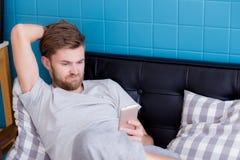 Hombre feliz que mira el medios contenido en un teléfono elegante que se sienta en el A.C. Imagen de archivo