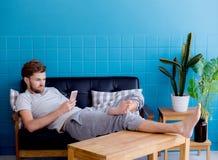 Hombre feliz que mira el medios contenido en un teléfono elegante que se sienta en un sofá en casa Fotografía de archivo libre de regalías