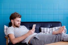 Hombre feliz que mira el medios contenido en un teléfono elegante que se sienta en un sofá en casa Foto de archivo libre de regalías