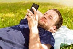 Hombre feliz que mira el teléfono móvil mientras que pone en hierba Fotos de archivo libres de regalías
