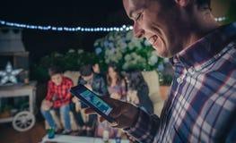 Hombre feliz que mira smartphone en un partido con los amigos Fotos de archivo libres de regalías