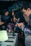 Hombre feliz que mira smartphone en un partido con los amigos Foto de archivo