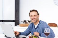 Hombre feliz que mira su computadora portátil durante almuerzo Foto de archivo