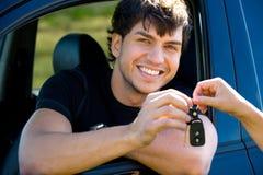 Hombre feliz que muestra claves en coche Imagen de archivo libre de regalías