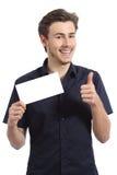 Hombre feliz que muestra una tarjeta en blanco que gesticula los pulgares para arriba Foto de archivo libre de regalías