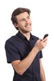 Hombre feliz que piensa mientras que usa un teléfono elegante Imagen de archivo