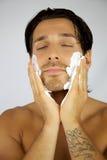 Hombre feliz que pone la crema de afeitar en su cara Fotografía de archivo libre de regalías