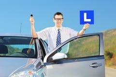 Hombre feliz que presenta cerca del coche, llevando a cabo L muestra y llave después que tienen h Foto de archivo libre de regalías