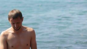 Hombre feliz que restaura en la agua de mar fresca, caminando hacia orilla, resto activo almacen de metraje de vídeo