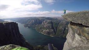 Hombre feliz que salta al borde del alto acantilado con el fiordo en fondo en Noruega metrajes