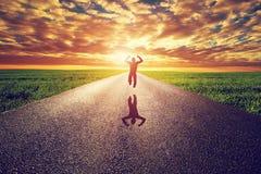 Hombre feliz que salta en el camino recto largo, manera hacia el sol de la puesta del sol Imagen de archivo libre de regalías